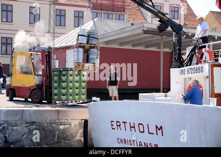 Ship unloading in Gudhjem on Bornholm, Denmark - Stock Photo