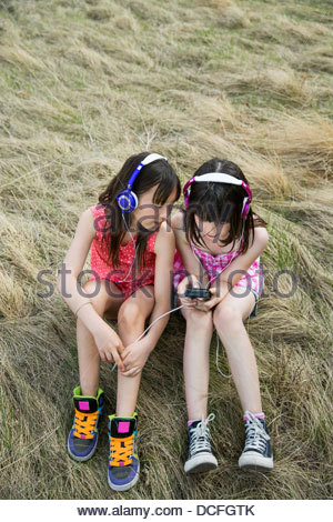 Girls sitting outside listening to music - Stock Photo