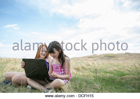 Girls using laptop outdoors - Stock Photo