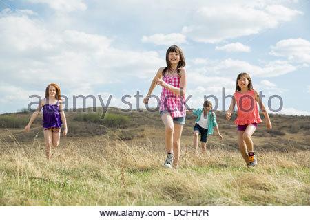 Young girls running through field - Stock Photo