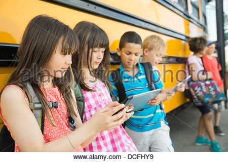 Schoolchildren using smart devices while waiting - Stock Photo
