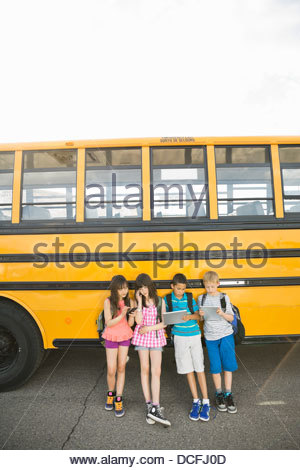 Schoolchildren using smart devices while waiting by school bus - Stock Photo
