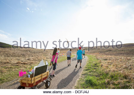 Children walking on path with wind turbines - Stock Photo