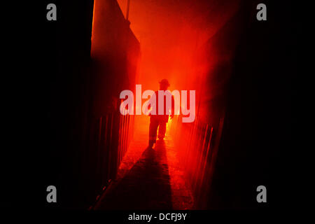 A New York Air National Guard firefighter ducks under flames in a burning building during training at the Suffolk - Stock Photo