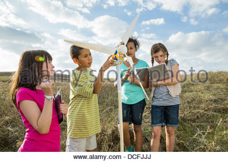 Schoolchildren using digital tablets while studying a wind turbine model - Stock Photo