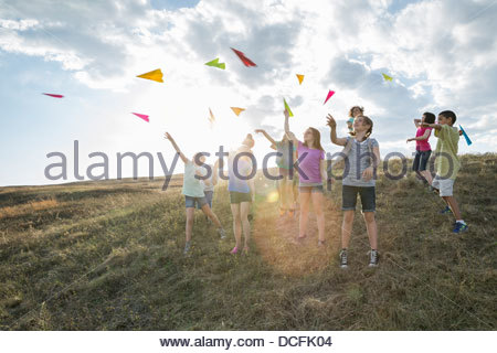 Group of kids outdoors throwing paper airplanes - Stock Photo