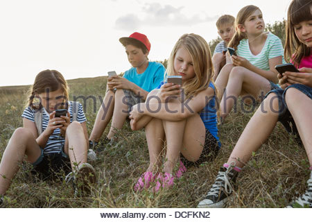 Group of kids using smart phones on a hillside - Stock Photo