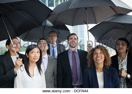Business team with umbrellas looking up - Stock Photo
