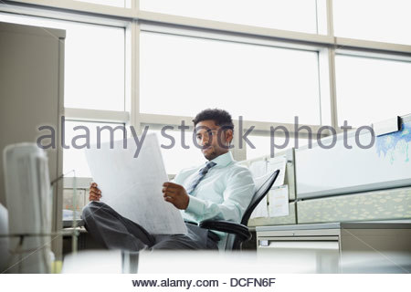 Businessman examining blueprint in cubicle at office - Stock Photo