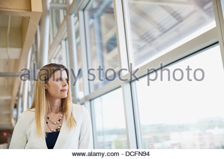 Thoughtful businesswoman looking out window - Stock Photo