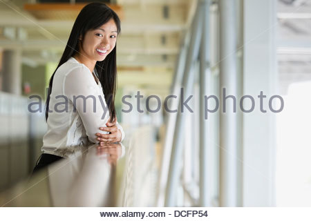 Businesswoman leaning on railing in office - Stock Photo