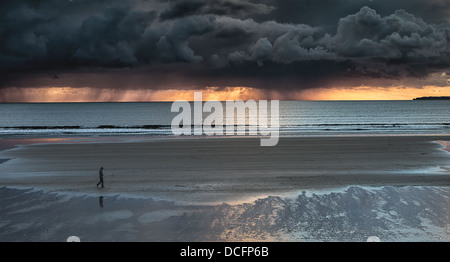Newgale beach in Pembrokshire Wales a Surfers paradise. storm clouds on horizon at sunset with light under clouds - Stock Photo