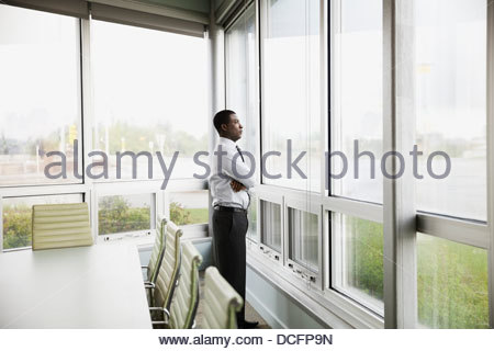 Side view of businessman looking out window - Stock Photo