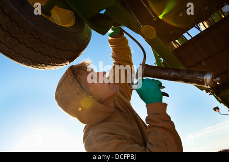 A Person Works On Farm Equipment; Three Hills, Alberta, Canada - Stock Photo
