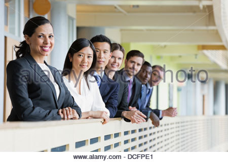 Smiling business colleagues standing in a row - Stock Photo