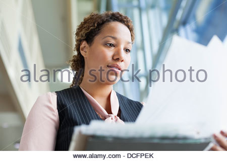 Businesswoman reviewing documents in office - Stock Photo
