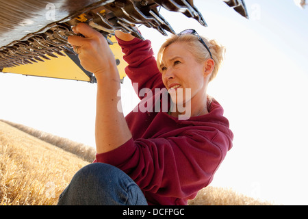 A Woman Works On Her Farm Equipment; Three Hills, Alberta, Canada - Stock Photo