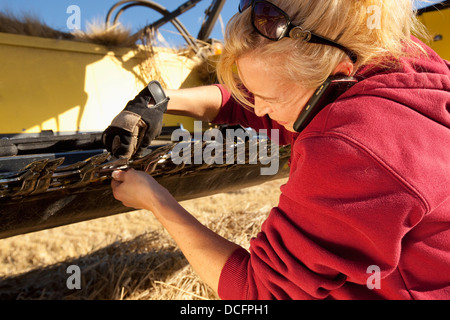 A Woman Works On Her Farm Equipment While Talking On Her Cell Phone; Three Hills, Alberta, Canada - Stock Photo