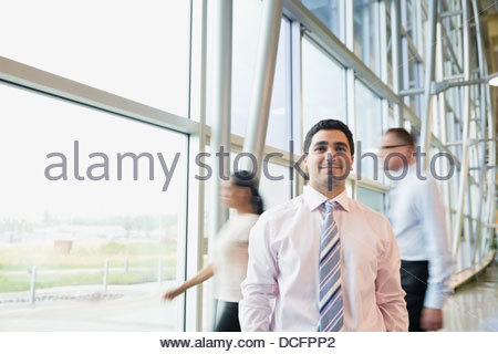 Portrait of confident businessman standing in office building - Stock Photo