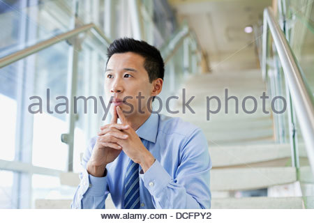 Thoughtful businessman sitting on staircase in office - Stock Photo
