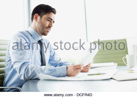 Businessman reviewing documents in board room - Stock Photo