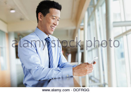 Smiling businessman reading text message - Stock Photo