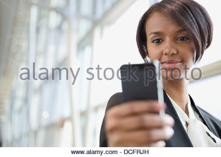 Businesswoman looking down at smart phone - Stock Photo