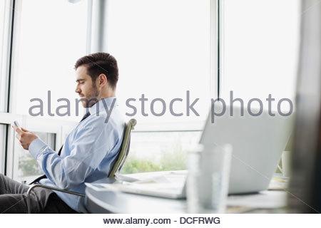 Businessman texting on smart phone - Stock Photo
