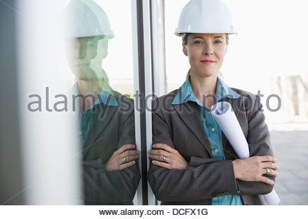 Confident engineer holding blueprints - Stock Photo