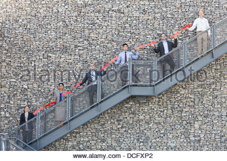 Business people forming upward arrow on staircase - Stock Photo