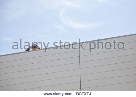 Businessman looking down through binoculars on rooftop - Stock Photo