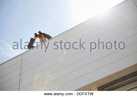 Businessman looking through binoculars on rooftop - Stock Photo