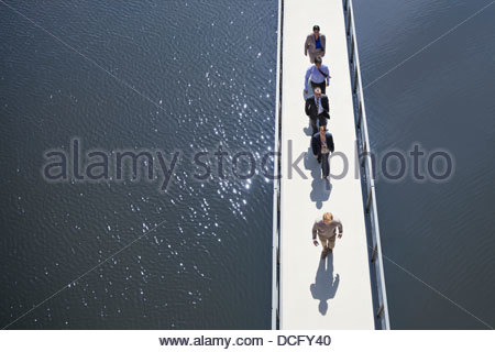 Business people walking in a row on a bridge - Stock Photo