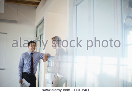 Co-workers talking around water cooler - Stock Photo