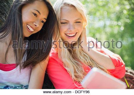 Teenage girls taking self-portrait at park - Stock Photo