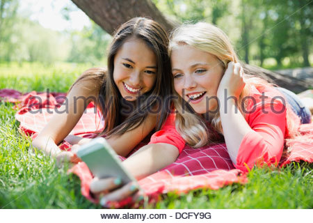 Teenagers using smart phone outdoors - Stock Photo