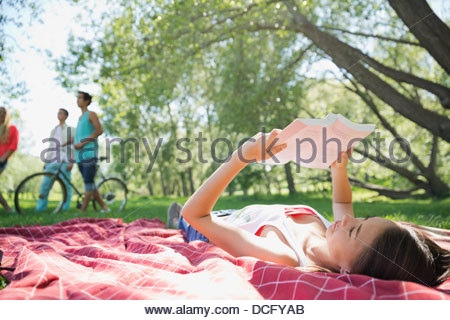 Teenage girl reading book in park - Stock Photo