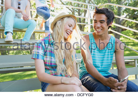 Teens laughing while using smart phone - Stock Photo