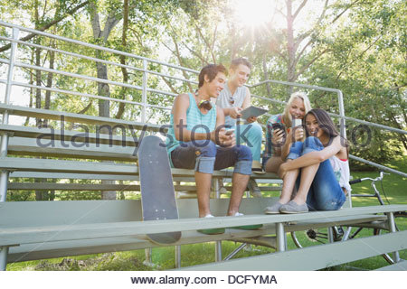 Teens using smart devices outdoors - Stock Photo