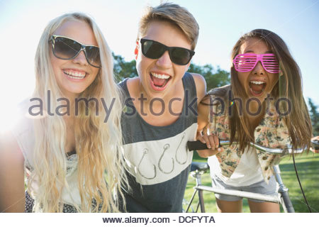 Portrait of playful teenage friends wearing shades in park - Stock Photo