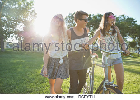 Happy teenage friends with bicycle walking in park - Stock Photo