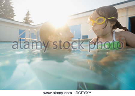 Man playing with daughter in swimming pool - Stock Photo