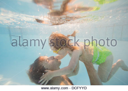 Father and daughter underwater in swimming pool - Stock Photo