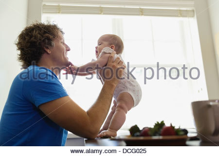 Side view of father playing with baby girl at home - Stock Photo