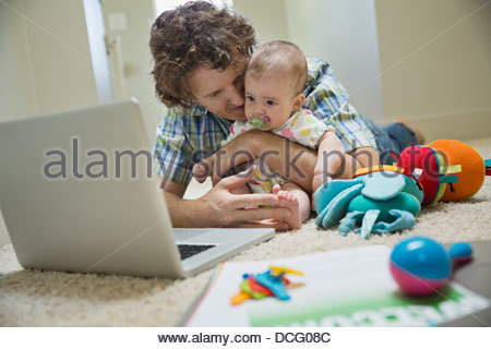 Father with baby girl looking at laptop - Stock Photo