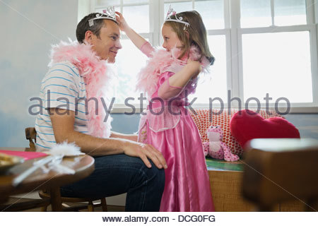 Little girl putting tiara on her dad - Stock Photo