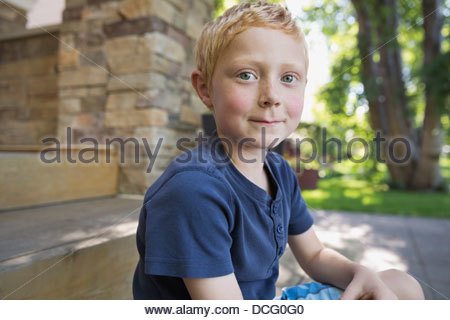 Portrait of cute little boy sitting in yard - Stock Photo