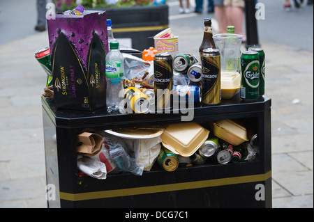 Overflowing litter bin on the street during Brecon Jazz Festival 2013 - Stock Photo