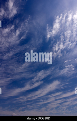 High wispy white cirrus mare's tail clouds against blue sky, UK - Stock Photo