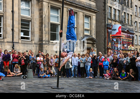 Acrobat performing a balancing act on a pole, Royal mile, Edinburgh Fringe Festival, Edinburgh, Scotland, United - Stock Photo